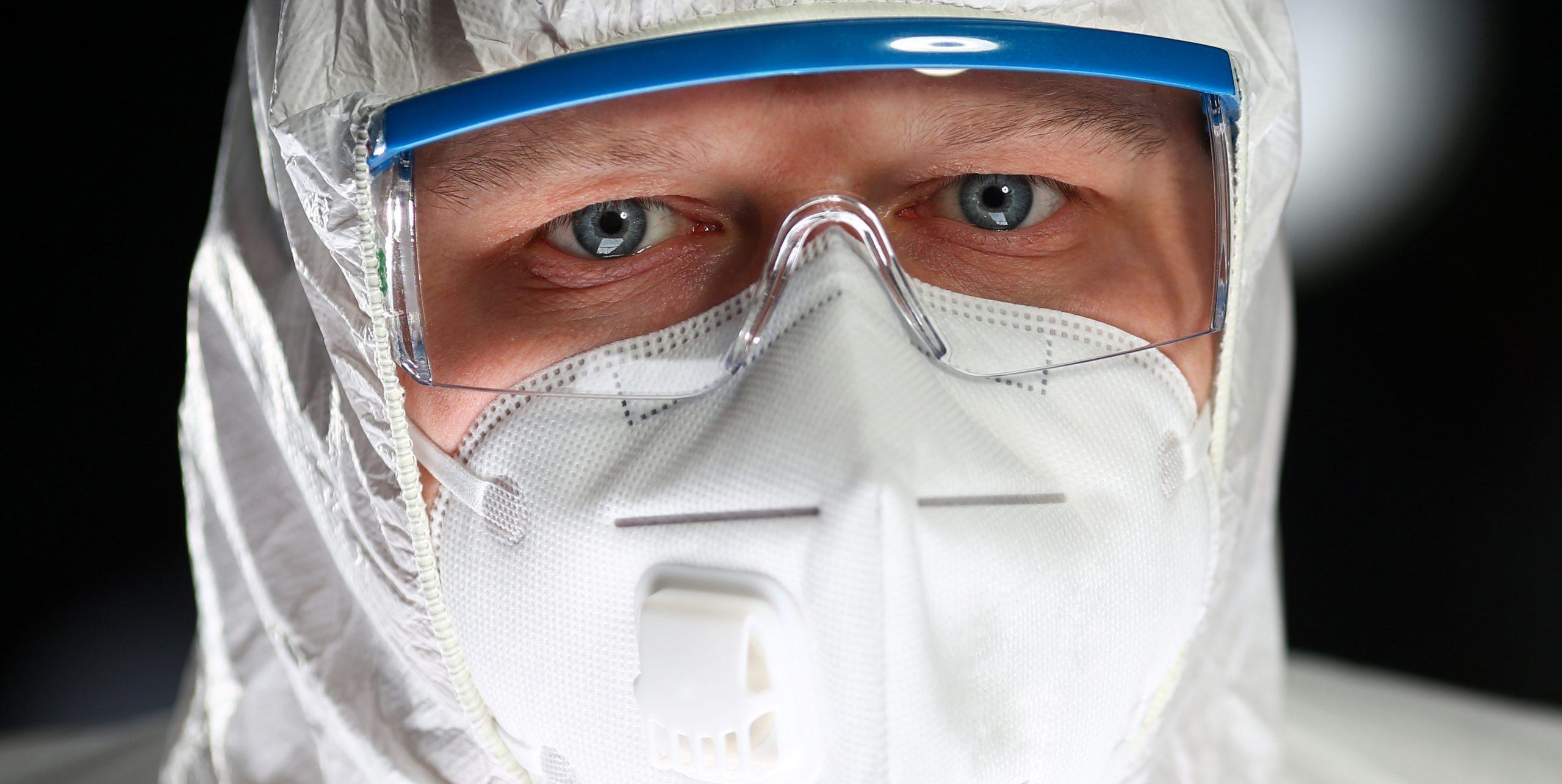 Nahaufname des Gesichts eines Mannes, der einen weißen Schutzanzug, eine Schutzbrille und eine FFP2-Maske trägt