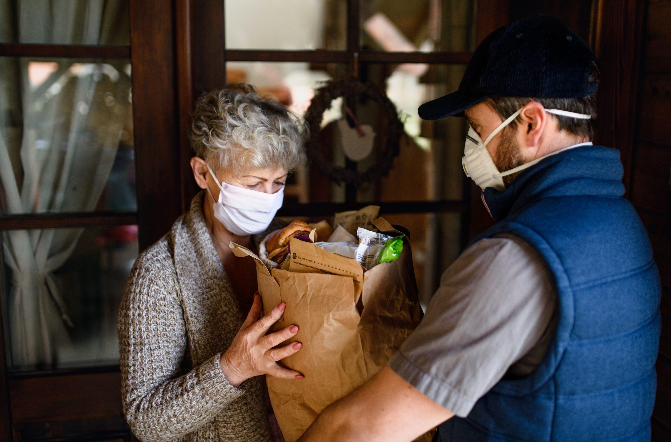 Ein Kurier, der einer älteren Dame ihre Einkäufe bringt. Beide tragen Gesichtsmasken.