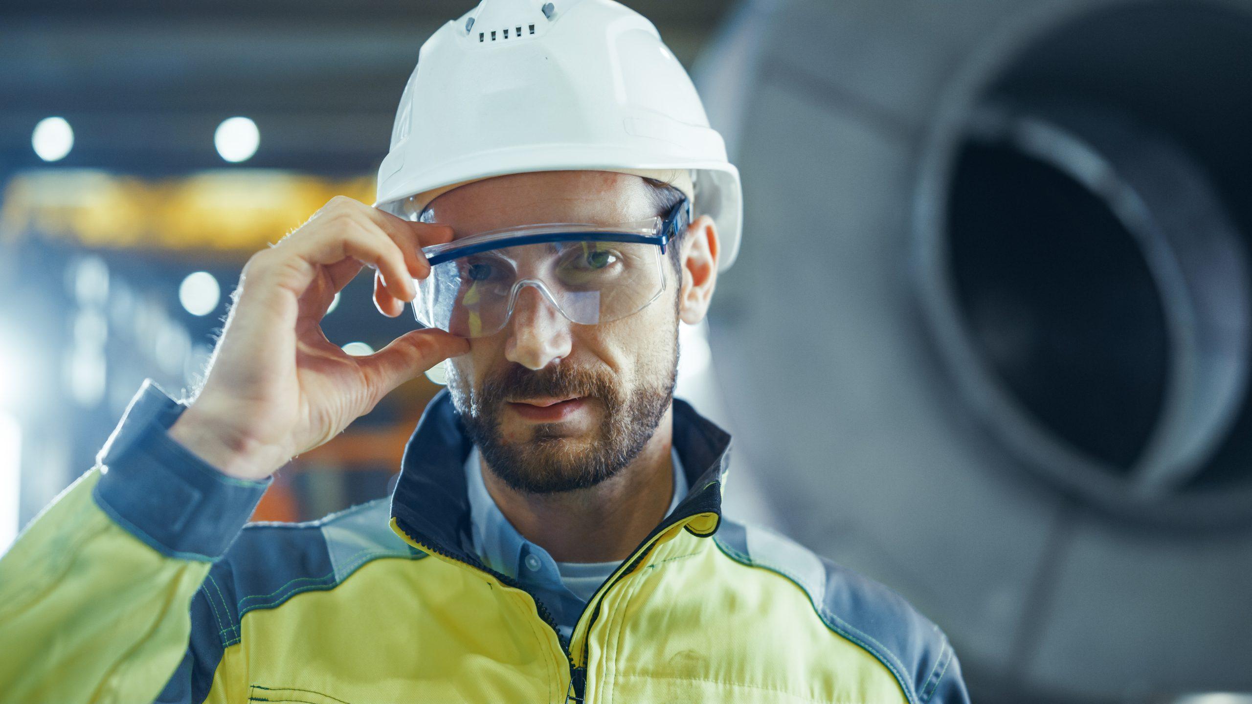 Portrait eines professionellen Ingenieur in der Industrie, der eine Schutzbrille und einen Schutzhelm trägt